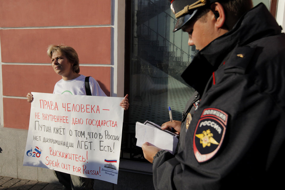 "In this Thursday, Sept. 5, 2013 photo, a Russian policeman checks ID of a gay rights activist holding a protest poster in downtown St. Petersburg, Russia. The poster reads "" Putin lies, saying that there is no gay discrimination in Russia."" (AP Photo/Elena Ignatyeva)"