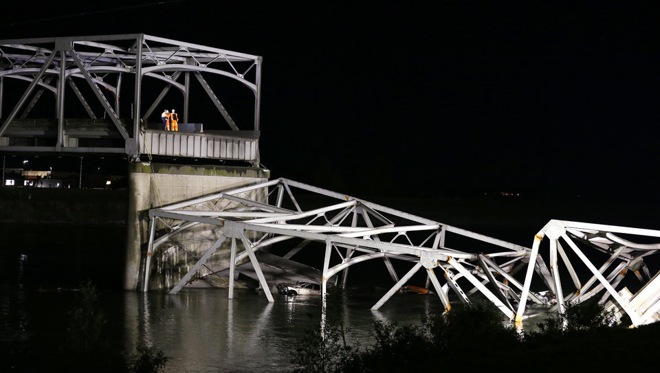 Photo - Officials look on from the remaining structure at the collapsed Interstate-5 bridge submerged below in the Skagit River in Mount Vernon, Wash., Thursday, May 23, 2013. At least two vehicles went into the river. (AP Photo/Elaine Thompson)