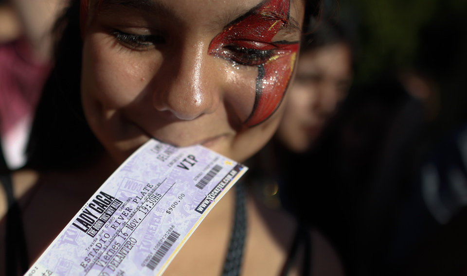 Photo -   A Lady Gaga fan holds her VIP ticket in her mouth as she stands outside the venue where the U.S. pop star will perform a concert, in Buenos Aires, Argentina, Friday, Nov. 16, 2012. The Latin American leg of her,