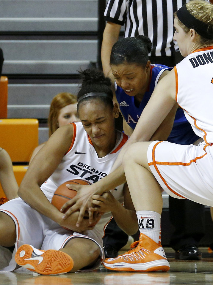 Photo - Oklahoma State's Kendra Suttles , left, and Liz Donohoe, at right, fight for control of the ball with Kansas' CeCe Harper during a women's college basketball game between Oklahoma State University (OSU) and Kansas at Gallagher-Iba Arena in Stillwater, Okla., Tuesday, Jan. 8, 2013. Oklahoma State won 76-59. Photo by Bryan Terry, The Oklahoman