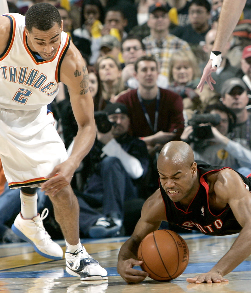 Photo - Oklahoma City's Thabo Sefolosha and  Toronto's Jarrett Jack chase down a loose ball during their NBA basketball game at the Ford Center in Oklahoma City on Sunday, Feb. 28, 2010. Photo by John Clanton, The Oklahoman
