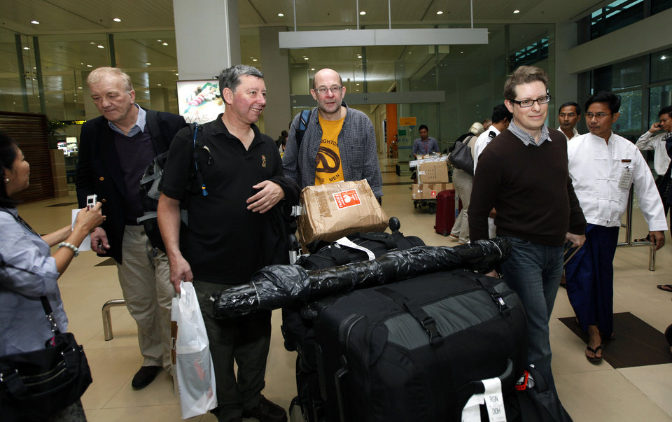 Photo - Farmer and businessman David Cundall, second from left, of Britain, arrives with his team of British excavators at Yangon International airport on Sunday, Jan. 6, 2013, in Yangon, Myanmar. The team arrived in Myanmar to begin the first of several digs they hope will unearth dozens of rare British fighter planes said to have been buried in the Southeast Asian country at the end of World War II. (AP Photo/Khin Maung Win)