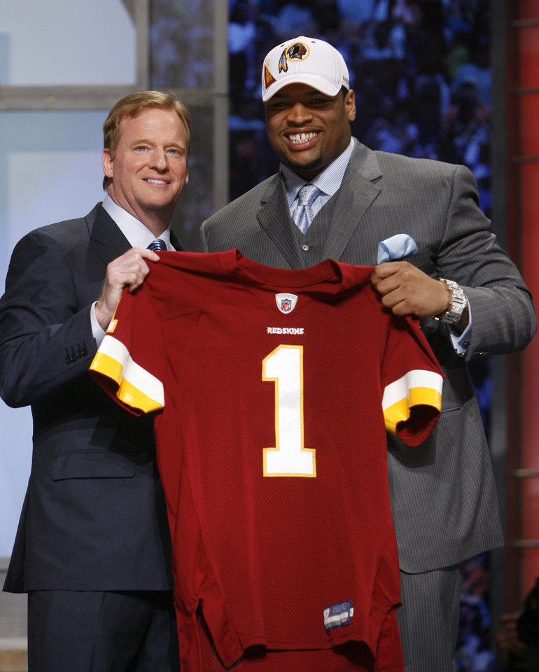 Photo - Oklahoma offensive tackle Trent Williams, right, holds up a jersey with NFL commissioner Roger Goodell  after he was selected as the fourth overall pick by the Washington Redskins in the first round of the NFL Draft at Radio City Music Hall Thursday, April 22, 2010, in New York. (AP Photo/Jason DeCrow)