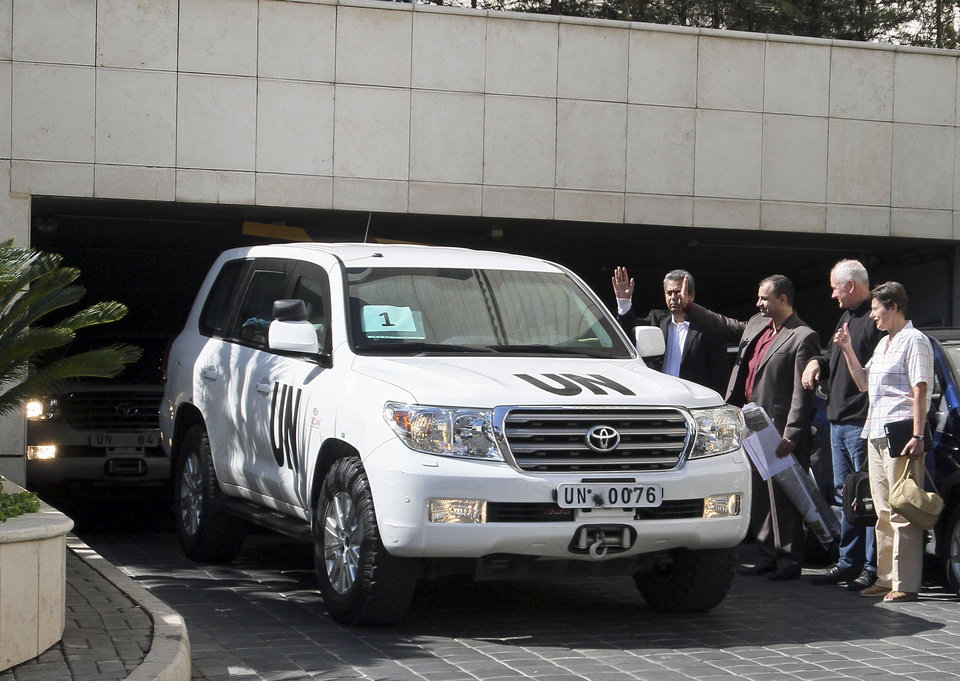 Photo - The head of UN inspectors' team, Professor Ake Sellstrom, second right, and Angela Kane, right, the representative on the United Nations for Disarmament Issues, watch as the UN inspectors' team leaves the Four Seasons hotel in Damascus, Syria, August 28, 2013. United Nations Secretary-General Ban Ki-moon pleaded for a diplomatic solution to the Syrian conflict, even as world powers appeared to be moving toward punitive military strikes against President Bashar Assad's regime for what the United States and its allies say was a deadly chemical weapons attack. Syria has denied it was behind the alleged attack. (AP Photo)