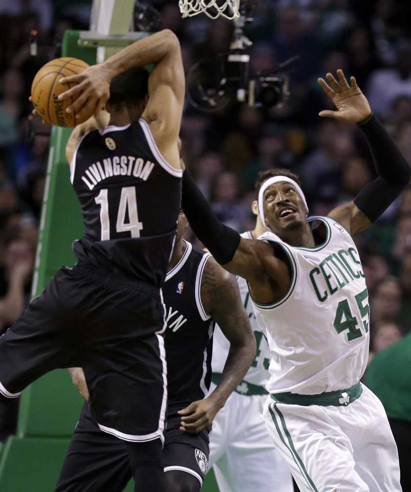Photo - Brooklyn Nets guard Shaun Livingston (14) vies for control of the ball with Boston Celtics forward Gerald Wallace (45) in the first quarter of an NBA basketball game, Sunday, Jan. 26, 2014, in Boston. (AP Photo/Steven Senne)