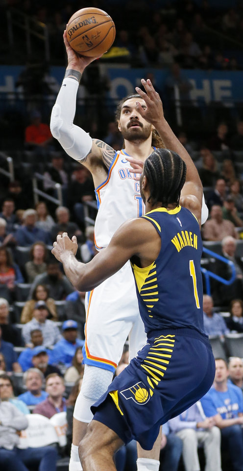 Photo - Oklahoma City's Steven Adams (12) shoots over Indiana's T.J. Warren (1) in the first quarter during an NBA basketball game between the Indiana Pacers and the Oklahoma City Thunder at Chesapeake Energy Arena in Oklahoma City, Wednesday, Dec. 4, 2019. [Nate Billings/The Oklahoman]
