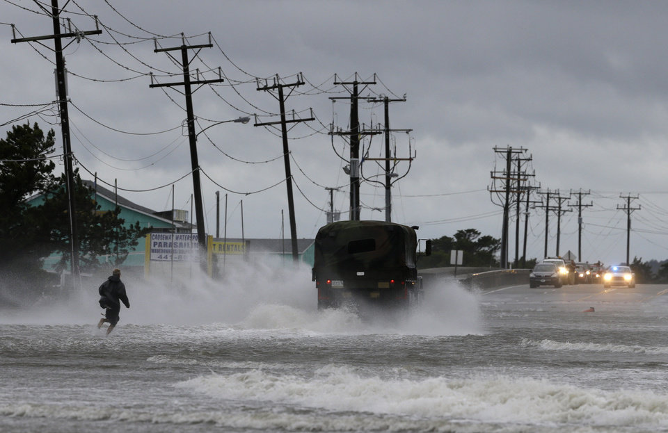Photo - A military vehicle and a man navigate a flooded Highway 64 as wind pushes water over the road while Hurricane Arthur passes through Nags Head, N.C., Friday, July 4, 2014. (AP Photo/Gerry Broome)