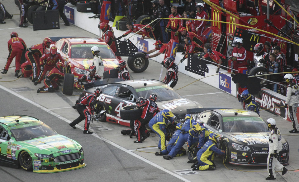 Photo - Pit crews work on the cars of AJ Allmendinger (47), Kurt Busch, center, and Jamie McMurray, rear, during the NASCAR Sprint Cup auto race at Richmond International Raceway in Richmond, Va., Saturday, April 26, 2014. (AP Photo/Jason Hirschfeld)