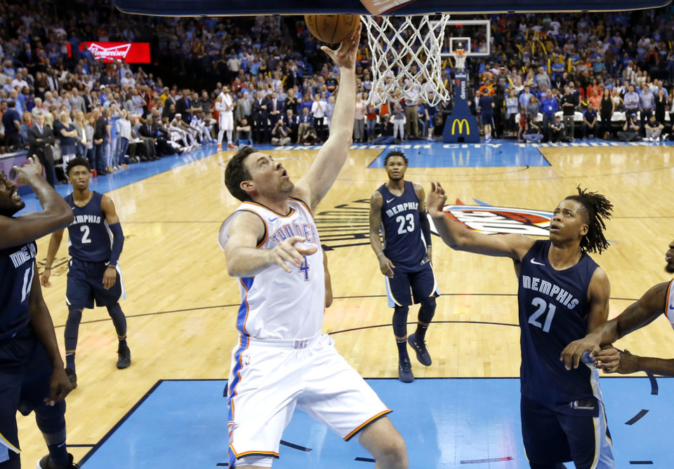 Photo - Oklahoma City's Nick Collison (4) goes to the basket beside Memphis' Deyonta Davis (21) during an NBA basketball game between the Oklahoma City Thunder and the Memphis Grizzlies at Chesapeake Energy Arena in Oklahoma City, Wednesday, April 11, 2018. Photo by Bryan Terry, The Oklahoman