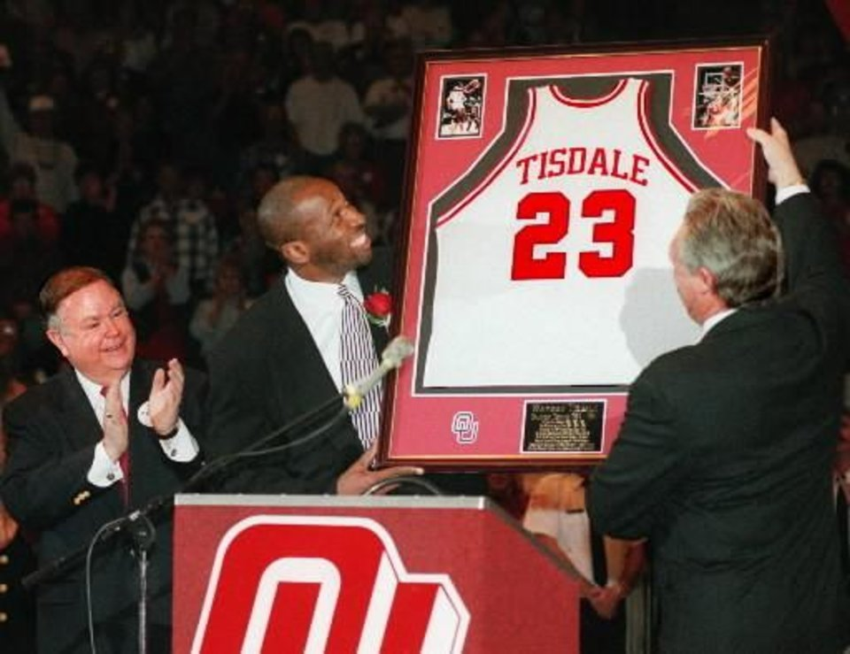 Photo - Former OU basketball star  Wayman  Tisdale smiles as he views his framed jersey that was unveiled before a record crowd inside the Lloyd Noble Arena during a halftime ceremony where his jersey (#23) was retired. To  Tisdale's right is OU athletic director Steve Owens.. At far left is OU president David Boren. Photo by Jim Beckel