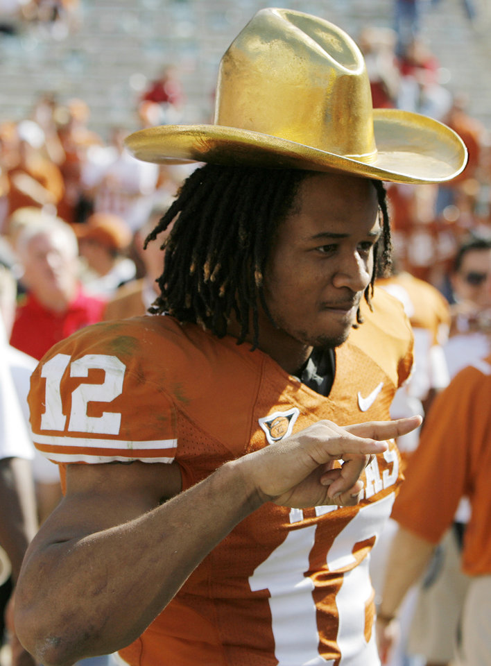 Photo - Earl Thomas (12) of Texas poses for a photo with the Golden Hat trophy after the Red River Rivalry college football game between the University of Oklahoma Sooners (OU) and the University of Texas Longhorns (UT) at the Cotton Bowl in Dallas, Texas, Saturday, Oct. 17, 2009. Texas won, 16-13. Photo by Nate Billings, The Oklahoman
