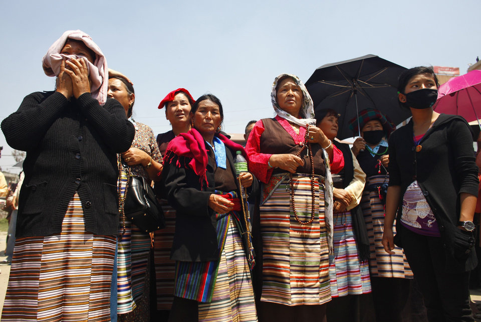 Photo - Relatives of Nepalese climbers killed in an avalanche on Mount Everest, wait for the funeral procession to begin in Katmandu, Nepal, Monday, April 21, 2014. Buddhist monks cremated the remains of Sherpa guides who were buried in the deadliest avalanche ever recorded on Mount Everest, a disaster that has prompted calls for a climbing boycott by Nepal's ethnic Sherpa community. The avalanche killed at least 13 Sherpas. Three other Sherpas remain missing and are presumed dead. (AP Photo/Niranjan Shrestha)