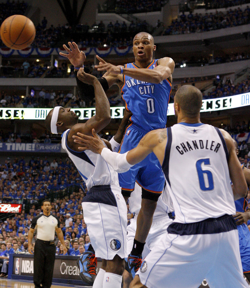 Oklahoma City\'s Russell Westbrook (0) passes the ball from between Jason Terry (31) of Dallas and Tyson Chandler (6) of Dallas during game 1 of the Western Conference Finals in the NBA basketball playoffs between the Dallas Mavericks and the Oklahoma City Thunder at American Airlines Center in Dallas, Tuesday, May 17, 2011. Photo by Bryan Terry, The Oklahoman