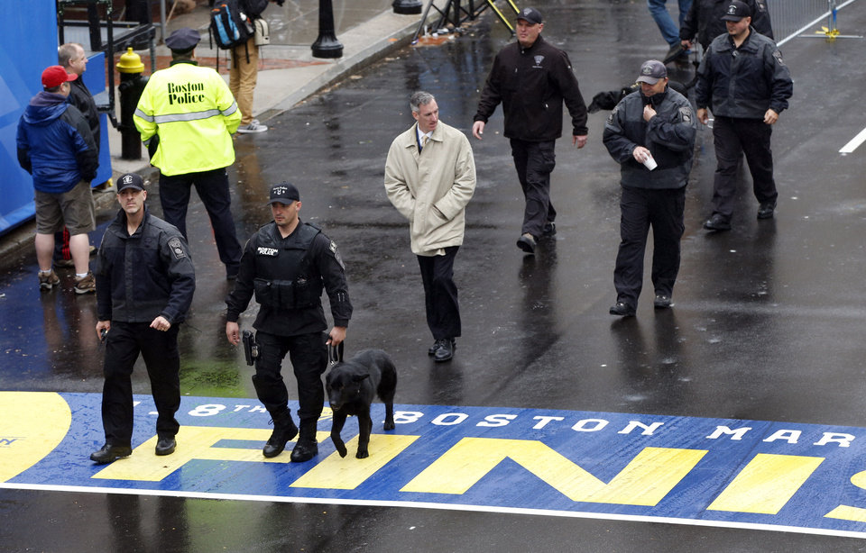 Photo - Security personnel walk across the Boston Marathon finish line prior to a remembrance ceremony for family members and survivors of the 2013 Boston Marathon bombing, on Boylston Street in Boston, Tuesday, April 15, 2014. (AP Photo/Elise Amendola)