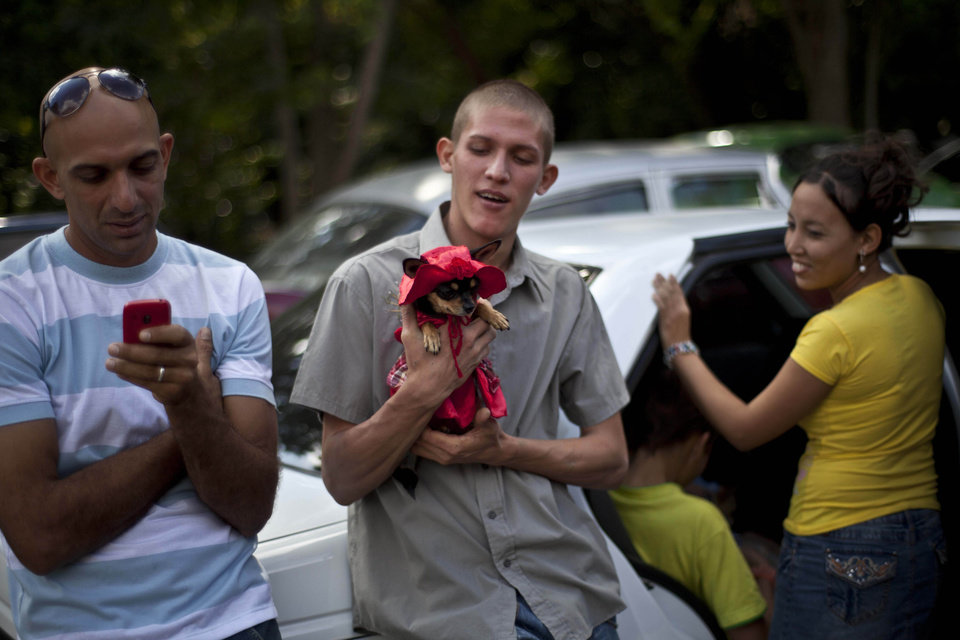 In this Nov. 25, 2012 photo, a man holds his chihuahua dog wearing a costume at the Fall Canine Expo in Havana, Cuba. Hundreds of people from all over Cuba and several other countries came for the four-day competition to show off their shih tzus, beagles, schnauzers and cocker spaniels that are the annual Fall Canine Expo's star attractions. (AP Photo/Ramon Espinosa)