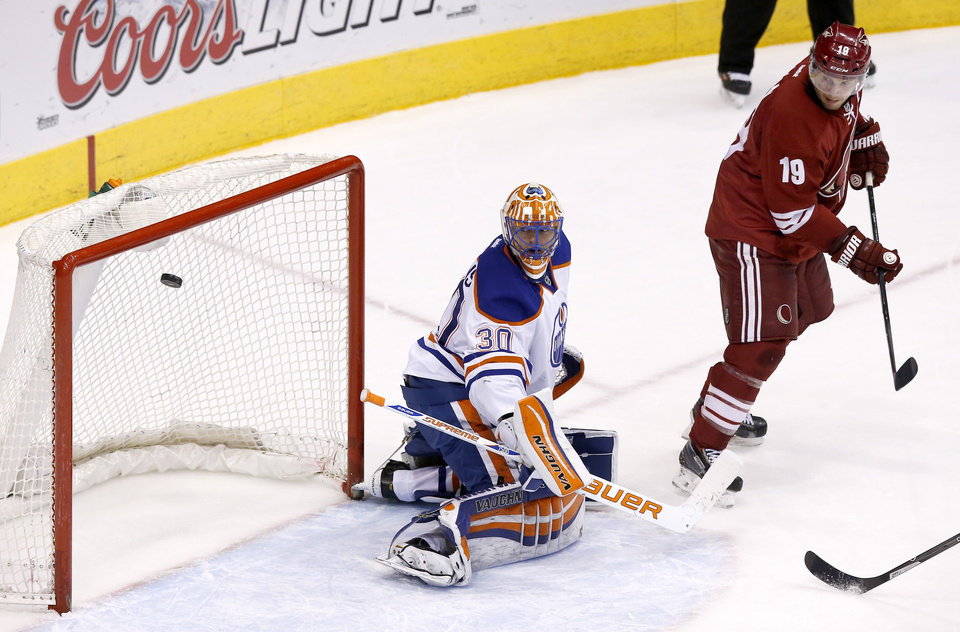 Photo - Edmonton Oilers goalie Ben Scrivens (30) gives up a goal to Phoenix Coyotes' Oliver Ekman-Larsson, not seen, as Coyotes' Shane Doan (19) watches during the second period of an NHL hockey game, Friday, April 4, 2014, in Glendale, Ariz. (AP Photo/Ross D. Franklin)