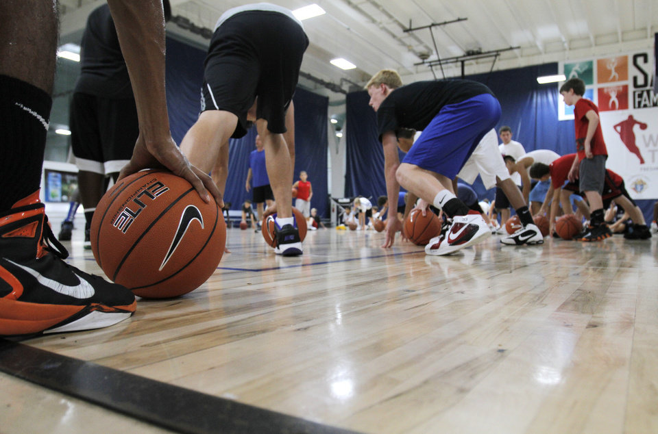 Photo - Campers participate in stretching drills during the Blake Griffin basketball camp at the Santa Fe Family Life Center in Oklahoma City Thursday, Aug. 4, 2011.  Photo by Garett Fisbeck, The Oklahoman