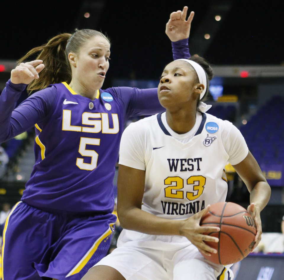 Photo - West Virginia guard Bria Holmes (23) looks for an opening to the goal as LSU guard Jeanne Kenney (5) defends in the first half of an NCAA college basketball second-round tournament game Tuesday, March 25, 2014, in Baton Rouge, La. (AP Photo/Rogelio V. Solis)