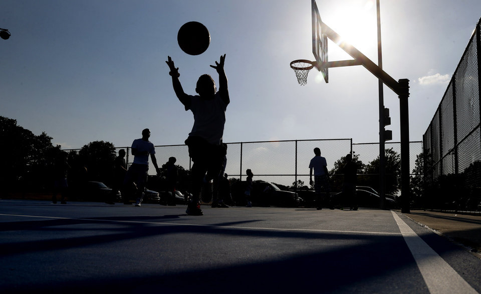 Photo -  Children play basketball on new public basketball courts after a grand opening ceremony in Midwest City. Photo by Bryan Terry, The Oklahoman   BRYAN TERRY -  THE OKLAHOMAN