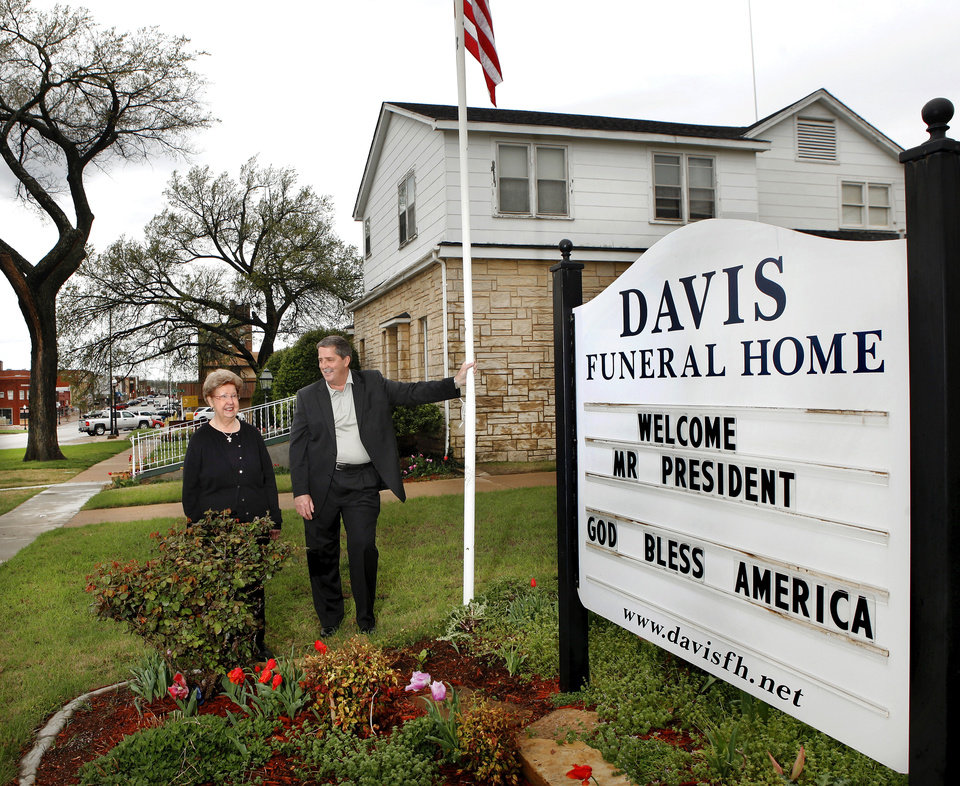Photo - .Ruth Ann Johnson, 73, left, who served 50 years as Cushing's librarian, says the Payne County community of 8,000 will welcome President Barack Obama on Thursday on his first visit to Oklahoma after being elected in 2008. Johnson talks with Rodger Floyd on Tuesday in front of his funeral home business in downtown Cushing. Floyd put a welcoming greeting for the president on his business marquee Tuesday morning.