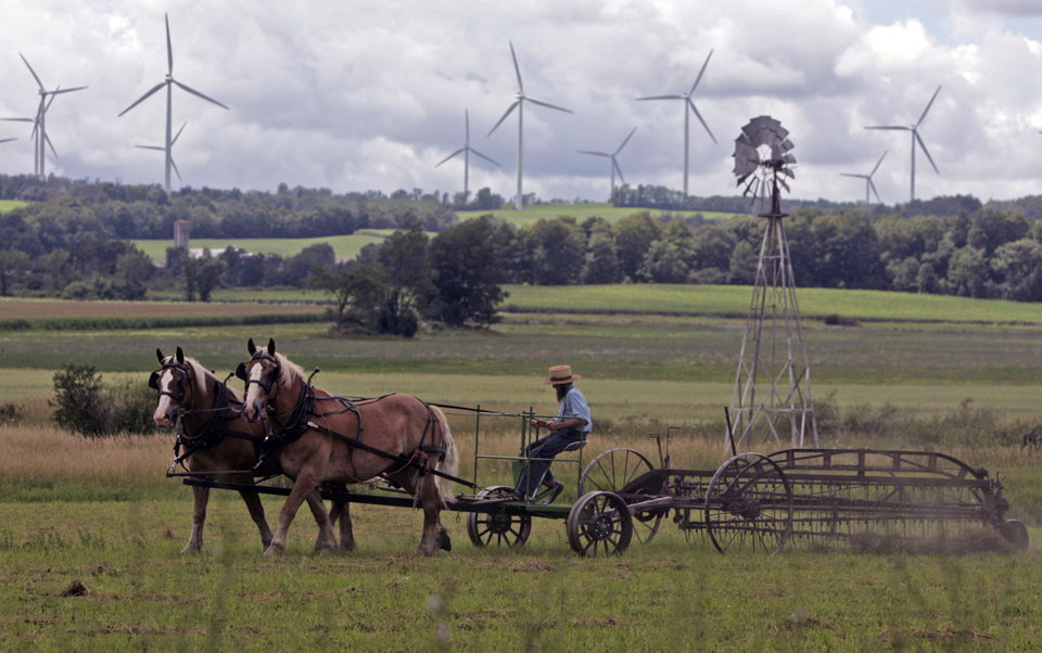 Photo - FILE - In this Aug. 4, 2008 file photo, an Amish farmer rakes hay as wind turbines from the Maple Ridge Wind Farm work in the distance in Lowville, N.Y. A new study says New York could be completely powered by wind, water and sunlight by 2030 with a concerted push, though the state's own decade-long effort to significantly boost green energy shows how difficult that would be in practice. (AP Photo/Mike Groll, File)