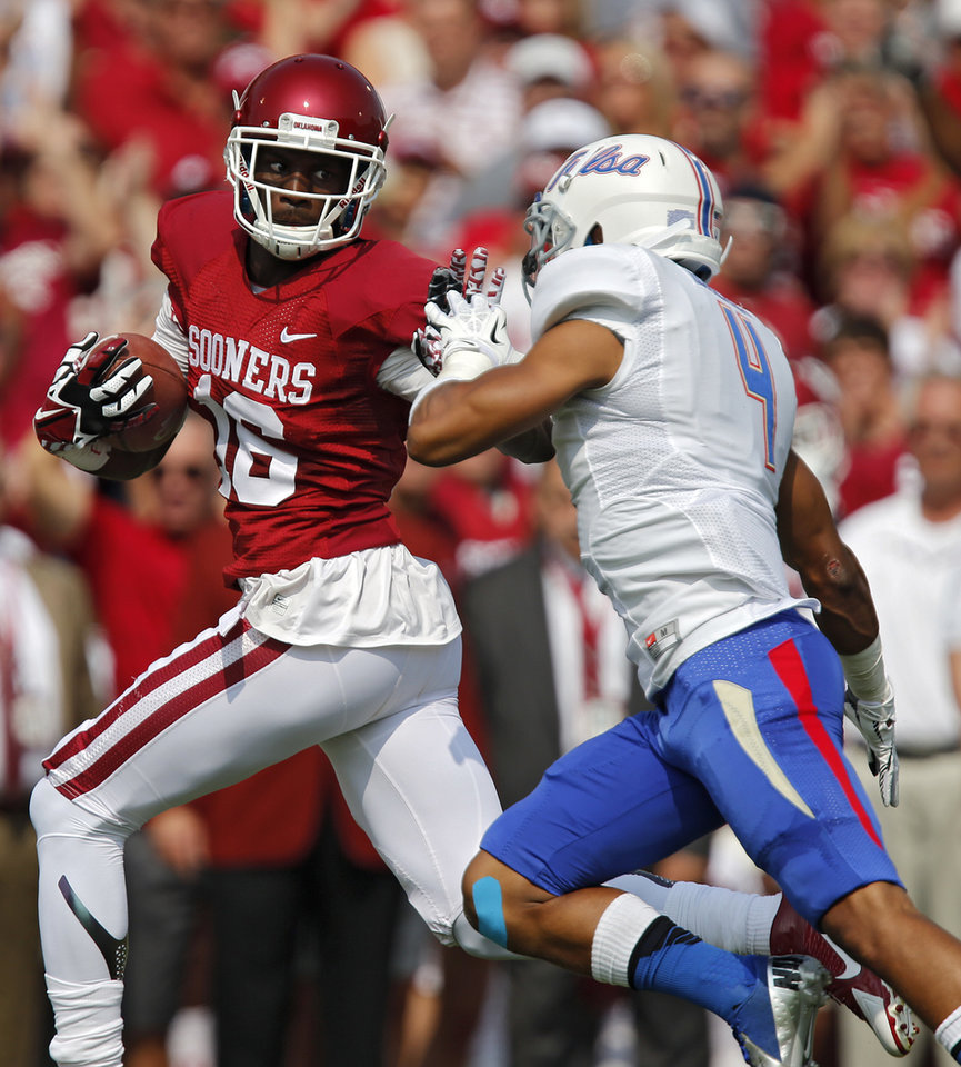 Photo - Oklahoma's Jaz Reynolds (16) stiff arms Tulsa 's Darnell Walker (4) during the college football game between the University of Oklahoma Sooners (OU) and the University of Tulsa Hurricanes (TU) at the Gaylord-Family Oklahoma Memorial Stadium on Saturday, Sept. 14, 2013 in Norman, Okla.  Photo by Chris Landsberger, The Oklahoman