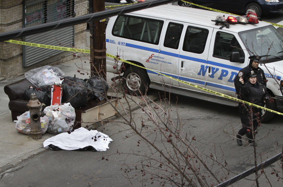 Photo - Police guard a sheet-covered plastic bag, left, on Eagle Avenue in the Bronx borough of New York, Tuesday, Feb. 26, 2013. A man out walking his dog early Tuesday morning discovered the dismembered remains of a woman in heavy duty plastic garbage bags, police said. The body is believed to be that of a 45-year-old woman. Her name was not immediately released, and the medical examiner's office was working to determine a cause of death.  (AP Photo/Bebeto Matthews)