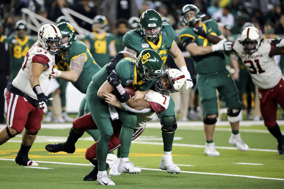 Photo - Baylor quarterback Charlie Brewer, left center, is sacked by Oklahoma defensive lineman Ronnie Perkins, right center, during the second half of an NCAA college football game in Waco, Texas, Saturday, Nov. 16, 2019. Oklahoma won 34-31. (AP Photo/Ray Carlin)