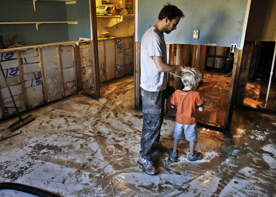 Photo - Local resident Chad Obrien comforts his four year old son Elijah, as he works to remove waterlogged and contaminated floors and walls from his flooded basement, which was wrecked in recent flooding, in Longmont, Colo., Wednesday Sept. 18, 2013. As water recedes and flows east onto the Colorado plains, rescuers are shifting their focus from emergency airlifts to trying to find the hundreds of people still unaccounted for after last week's devastating flooding. (AP Photo/Brennan Linsley)