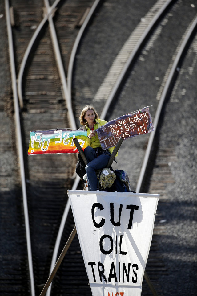 Photo - Abby Brockway sits atop a tripod erected on train tracks Tuesday, Sept. 2, 2014, in Everett, Wash. About a dozen demonstrators blocked the tracks at a Burlington Northern Santa Fe yard to protest oil and coal export terminals in the Northwest. (AP Photo/Elaine Thompson)