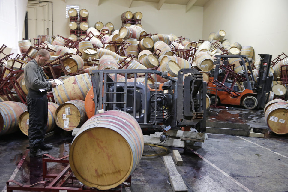 Photo - Cellar worker Adam Craig looks over some of the hundreds of earthquake damaged wine barrels that covered and toppled a pair of forklifts at the Kieu Hoang Winery Monday, Aug. 25, 2014, in Napa, Calif. A powerful earthquake that struck the heart of California's wine country caught many people sound asleep, sending dressers, mirrors and pictures crashing down around them and toppling wine bottles in vineyards around the region. The magnitude-6.0 quake struck at 3:20 a.m. PDT Sunday near the city of Napa. (AP Photo/Eric Risberg)