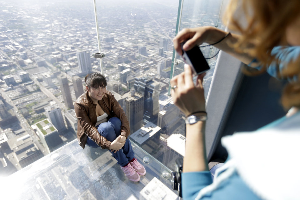 Photo - A tourist is photographed on the floor of one of four transparent ledges that jut out from the 103rd floor of the Willis Tower in Chicago on Thursday, May 29, 2014. The see-through glass bays known as The Ledge were designed with a protective coating that completely covers all glass surfaces to protect against scratches. One of the coatings cracked Wednesday night when a family was standing on it. Officials say the family wasn't in danger and the coating does not affect the structural integrity of the enclosure. (AP Photo/M. Spencer Green)