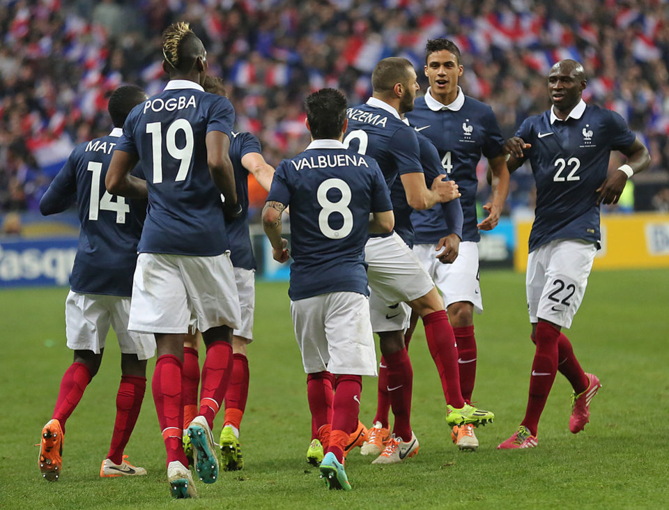Photo - French team players celebrate after Karim Benzema scored the first goal for France, during the friendly soccer match between France and Netherlands at the Stade de France, in Saint Denis, north of Paris, Wednesday March 5, 2014. Standing at right are:Eliaquim Mangala and Raphael Varane.(AP Photo/Remy de la Mauviniere)
