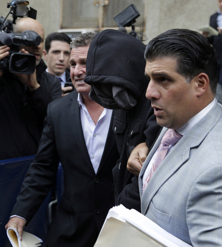 Photo - Wojciech Braszczok, center, with face covered, leaves the courthouse in New York, Wednesday, Oct. 9, 2013. Braszczok, an undercover police detective, was charged with gang assault in a motorcycle rally that descended into violence in New York. (AP Photo/Seth Wenig)