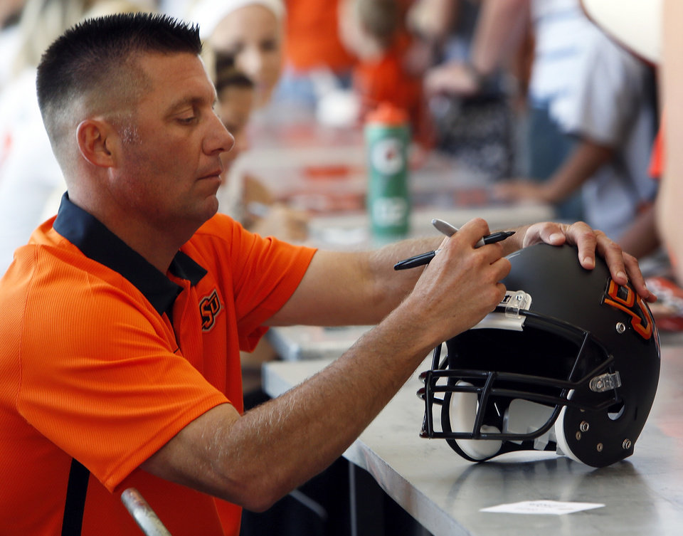 Photo - Oklahoma State head football coach Mike Gundy signs a helmet for a fan during OSU Fan Appreciation Day at Gallagher-Iba Arena in Stillwater, Okla., Saturday, Aug. 4, 2012. Photo by Nate Billings, The Oklahoman
