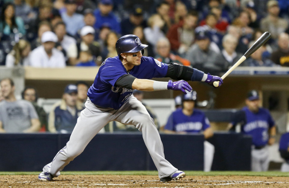 Photo - Colorado Rockies' Troy Tulowitzki reaches out to slap a single to left field against the San Diego Padres in the fifth inning of a baseball game Monday, April 14, 2014, in San Diego. (AP Photo/Lenny Ignelzi)