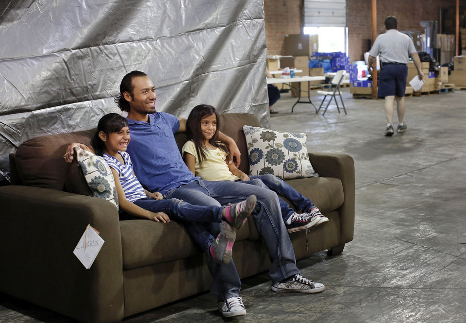 Photo - Elias Garcia and his two daughters, Jennifer, 7, and Fabiola, 8, sit on a new sofa while waiting for their furniture at the