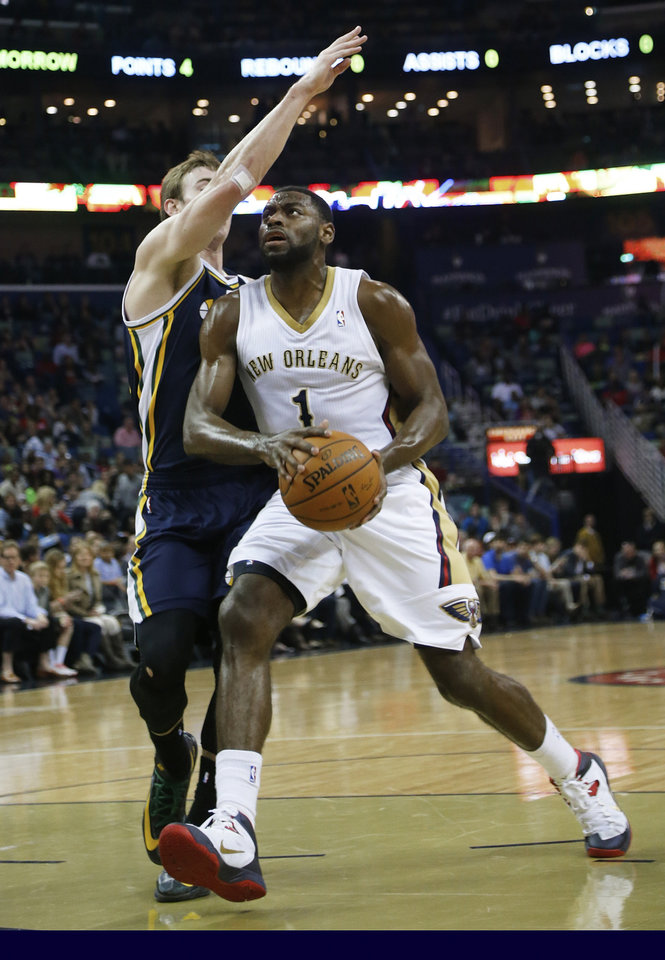 Photo - New Orleans Pelicans forward Tyreke Evans (1) drives to the basket around Utah Jazz guard Gordon Hayward (20) in the first half of an NBA basketball game in New Orleans, Friday, March 28, 2014. The Pelicans defeated the Jazz 102-95. (AP Photo/Bill Haber)
