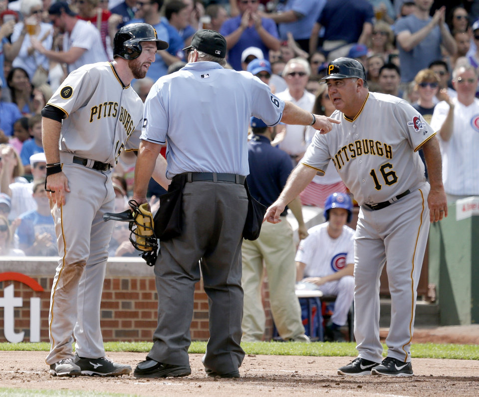 Photo - Pittsburgh Pirates' Ike Davis, left, and third base coach Nick Leyva, right, appeal to home plate umpire Bob Davidson, Davidson's call that Davis was out at home, during the second inning of a baseball game on Friday, June 20, 2014, in Chicago. The play was upheld in video review.  (AP Photo/Charles Rex Arbogast)