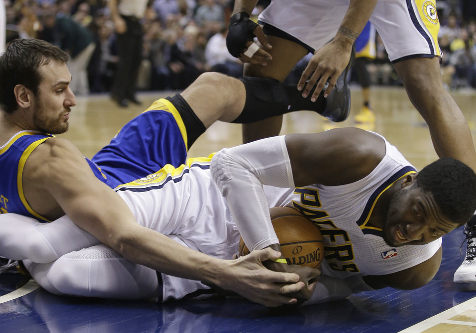 Photo - Indiana Pacers' Roy Hibbert, right, battles for a loose ball against Golden State Warriors' Andrew Bogut during the first half of an NBA basketball game Tuesday, March 4, 2014, in Indianapolis. (AP Photo/Darron Cummings)