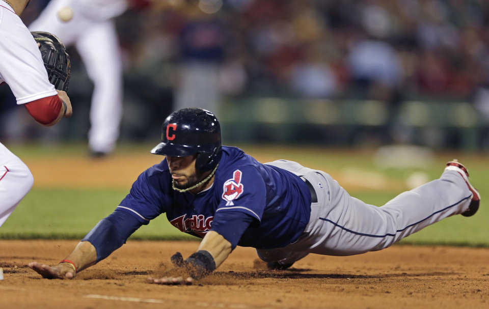 Photo - Cleveland Indians' Mike Aviles dives safely back to first base on a pick-off attempt during the fifth inning of a baseball game against the Boston Red Sox at Fenway Park in Boston, Thursday, May 23, 2013. (AP Photo/Charles Krupa)