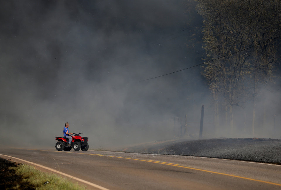 Photo - A man drives pass where is home was as grassfire overtakes the area near East Seward Road and Oak Hill Road,  Sunday, May 4, 2014. Photo by Sarah Phipps, The Oklahoman