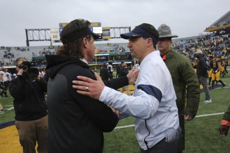 Photo -  OSU coach Mike Gundy, left, shakes hands with West Virginia coach Neal Brown after the Cowboys' 20-13 victory Saturday. The night before, Gundy was in Yukon to watch his son, Gunnar, quarterback Stillwater High to a playoff win. [AP PHOTO]