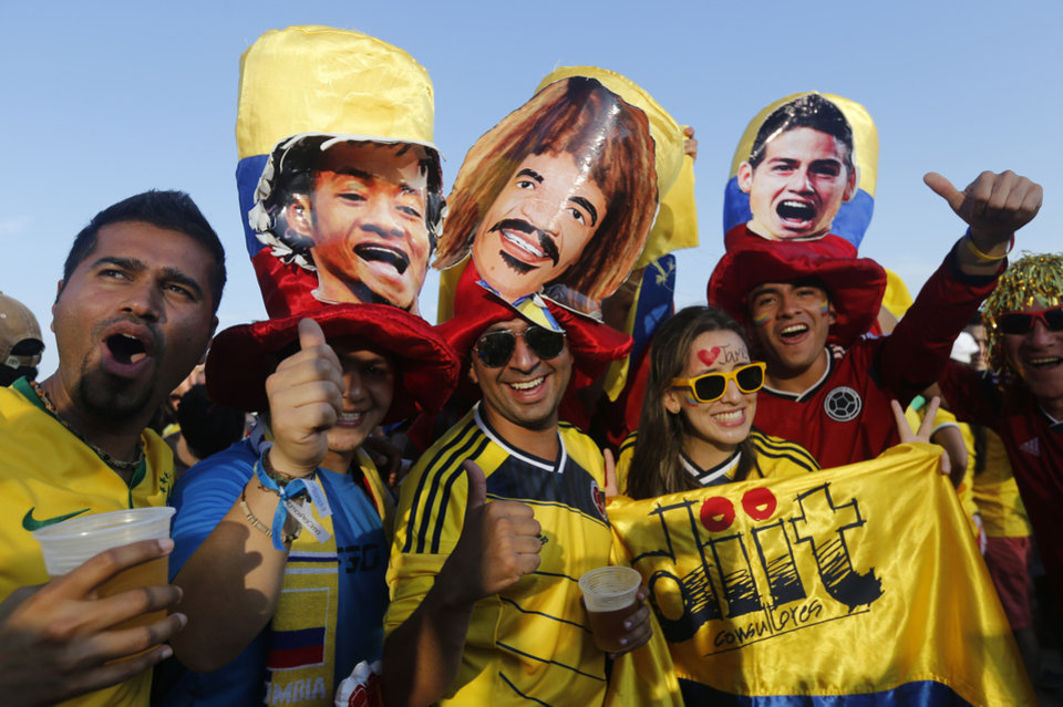 Photo - Soccer fans pose for a photo donning hats featuring cutouts of Colombian soccer stars, as they wait for the live broadcast of the World Cup quarterfinals' match between Brazil and Colombia, inside the FIFA Fan Fest area on Copacabana beach, in Rio de Janeiro, Brazil, Friday, July 4, 2014. (AP Photo/Silvia Izquierdo)