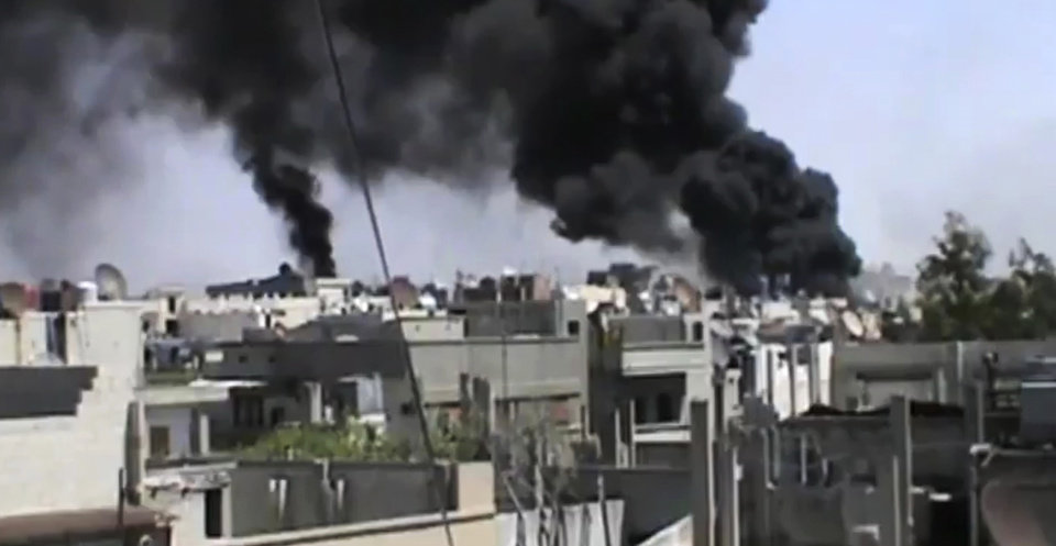 Photo -   In this image made from amateur video released by the Shaam News Network and accessed Wednesday, April 18, 2012, black smoke rises from buildings in Khaldiyeh district, Homs, Syria. Nearly a week after a cease-fire took effect, Syrian troops pounded a rebel stronghold Wednesday as the country's foreign minister met with his Chinese counterpart in Beijing during the latest round of talks aimed at preventing the truce from unraveling. (AP Photo/Shaam News Network via AP video) TV OUT, THE ASSOCIATED PRESS CANNOT INDEPENDENTLY VERIFY THE CONTENT, DATE, LOCATION OR AUTHENTICITY OF THIS MATERIAL