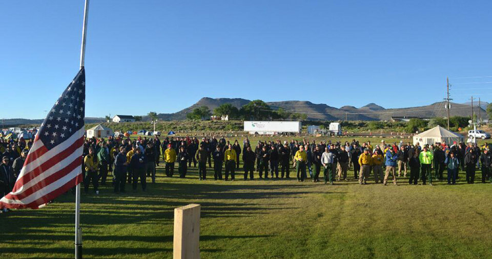 Photo - In a photo provided by the Rio Grande National Forest, firefighting personnel at the West Fork Complex Incident Command in Del Norte, Colo., observe a moment of silence early Monday morning, July 1, 2013, for fellow firefighters killed Sunday fighting a wildfire in Yarnell, Ariz.  The out-of-control blaze killed 19 firefighters, nearly all of them members of an elite crew of