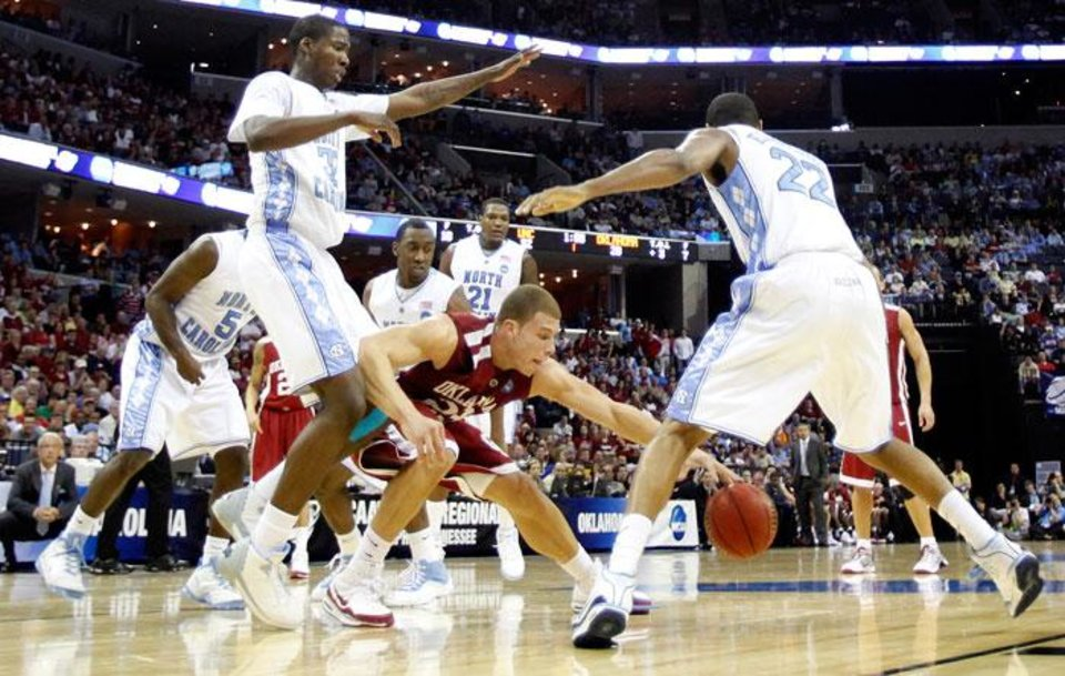 Photo -  Oklahoma's Blake Griffin (23) looses the ball under the defensive pressuer of North Carolina's Ed Davis (32) and Wayne Ellington (22) during the first half in the Elite Eight game of NCAA Men's Basketball Regional between the University of North Carolina and the University of Oklahoma at the FedEx Forum on Sunday, March 29, 2009, in Memphis, Tenn.  PHOTO BY CHRIS LANDSBERGER, THE OKLAHOMAN