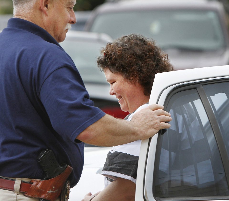 Photo - Former McLoud school teacher Kim Crain, shown here being helped out of a police car  by Lincoln County Deputy Dave Balleweg,  and her alleged accomplice, Gary Doby, a former professor at OBU,  arrive at the  Pottawatomie County Courthouse Monday morning, May 21, 2012,  for a preliminary hearing. Photo by Jim Beckel, The Oklahoman