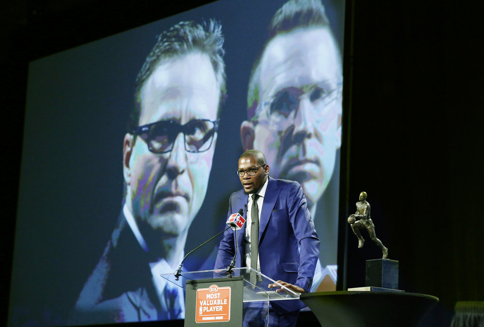 Oklahoma City Thunder head coach Scott Brooks, left, and General Manager Sam Presti, right, are pictured on a large video screen behind Thunder's Kevin Durant, center, as Durant speaks during the news conference announcing Durant is the winner of the 2013-14 Kia NBA Basketball Most Value Player Award in Oklahoma City, Tuesday, May 6, 2014. (AP Photo/Sue Ogrocki)