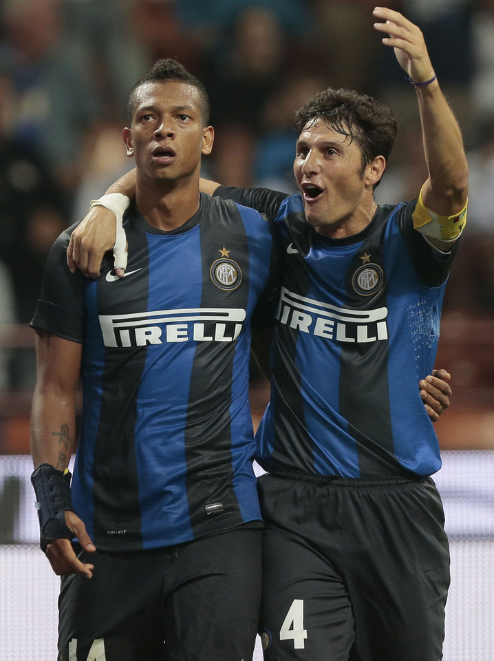 Photo -   Inter Milan midfielder Fredy Guarin, of Colombia, left, celebrates with teammate Javier Zanetti after scoring a goal during an Europa League play-off second leg soccer match between Inter Milan and Vaslui, at the San Siro stadium in Milan, Italy, Thursday, Aug. 30, 2012. (AP Photo/Emilio Andreoli)